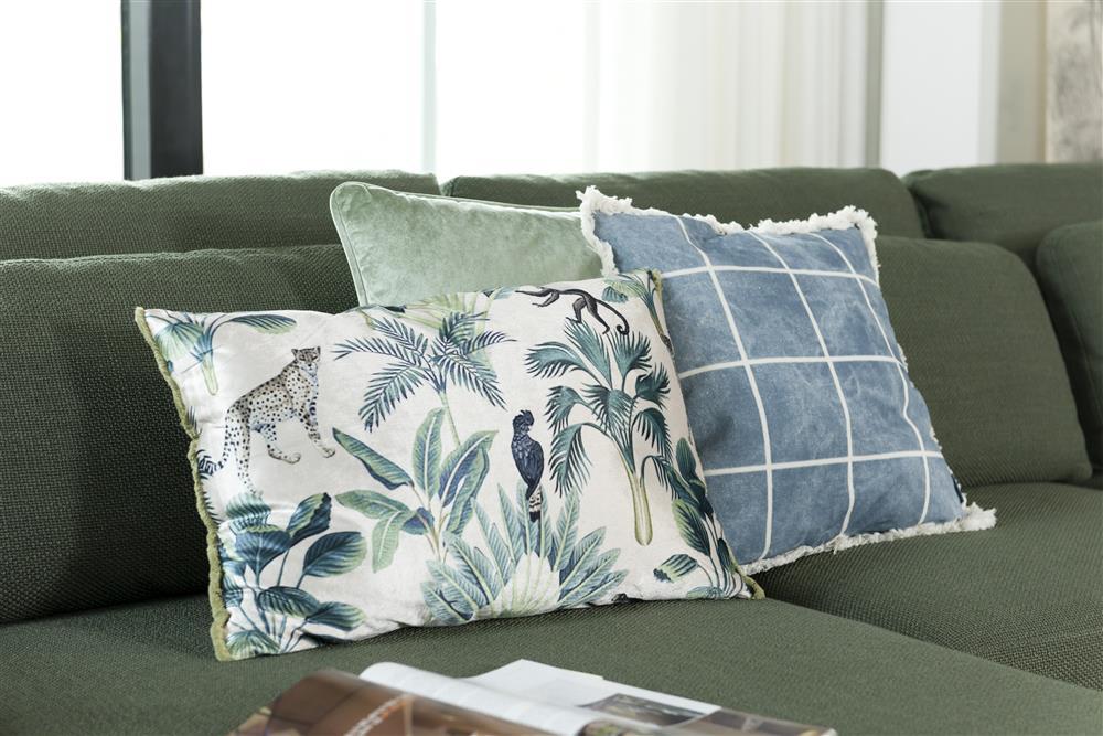 Assortiment de coussin à motifs sur canapé en tissus vert