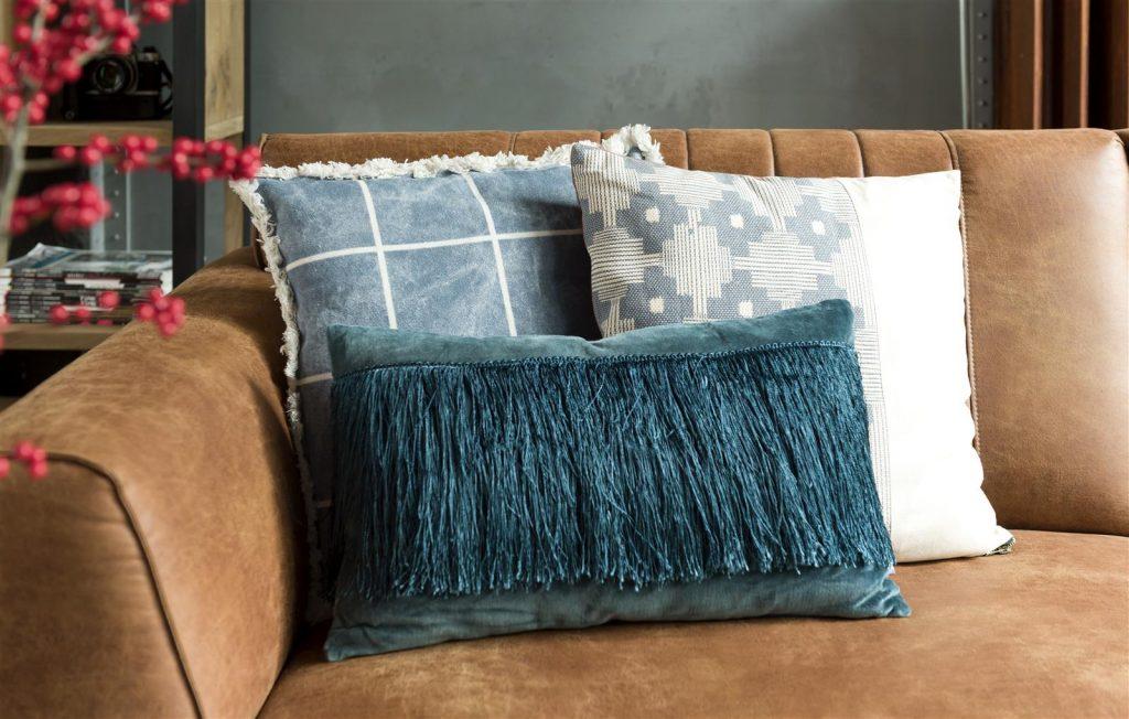 Assortiment de coussins bleus sur canapé en cuir marron