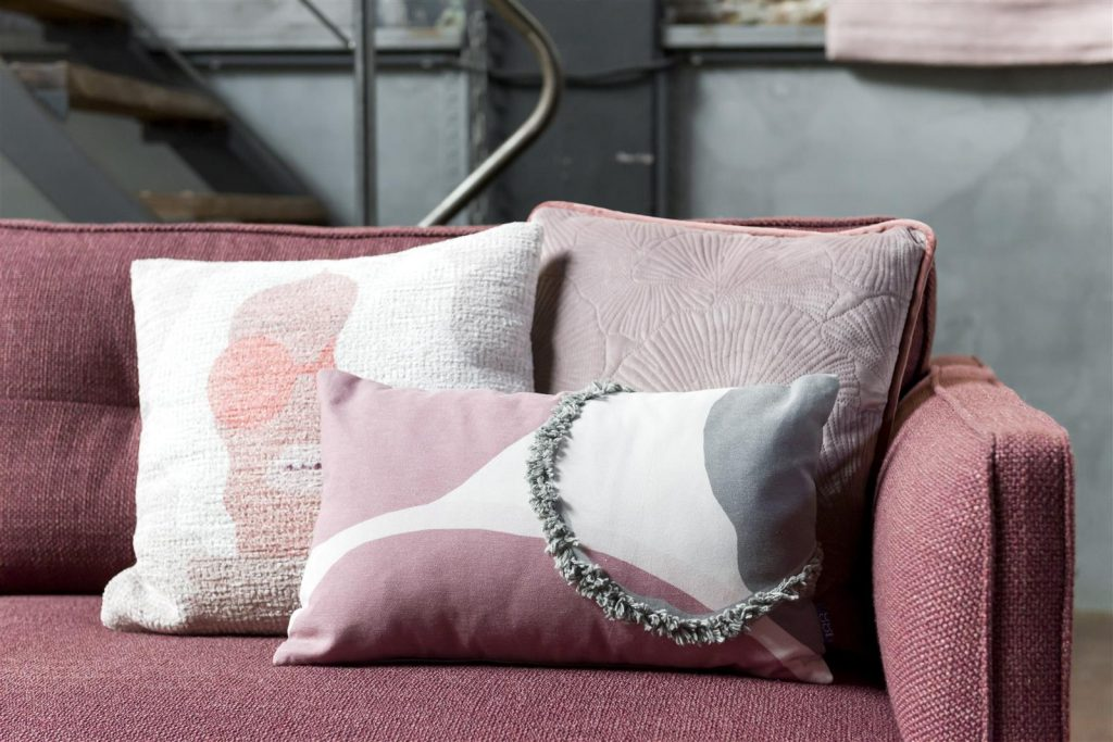 Assortiment de coussin gris et rose sur canapé en tissu rose