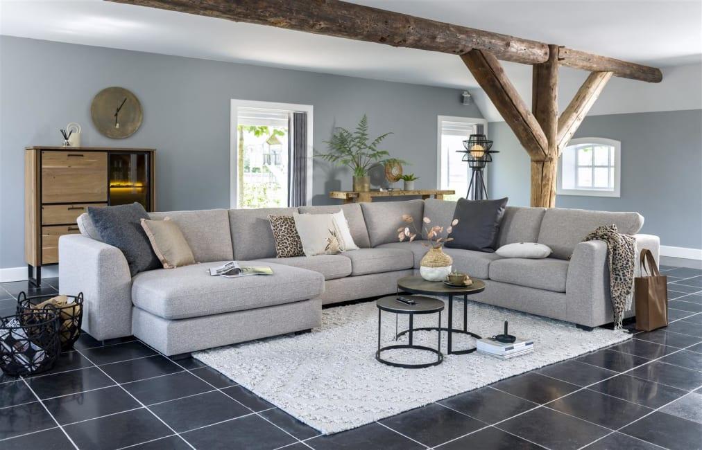 Ambiance salon moderne et chaleureux avec grand canapé d'angle en tissu gris clair
